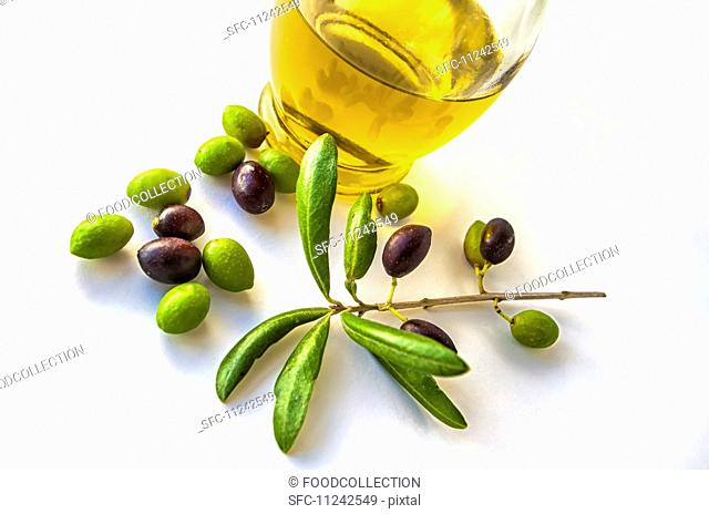 Some olives with an olive branch and a container with olive oil