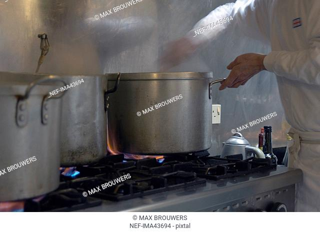 A cook cooking food in the kitchen of a restaurant