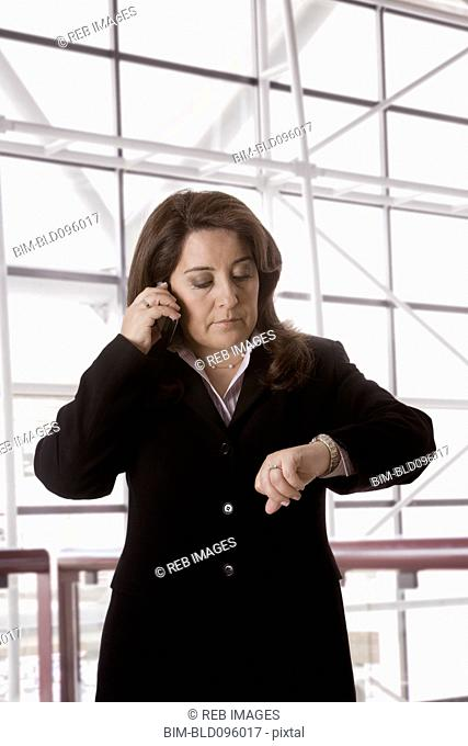 Hispanic businesswoman talking on cell phone checking the time