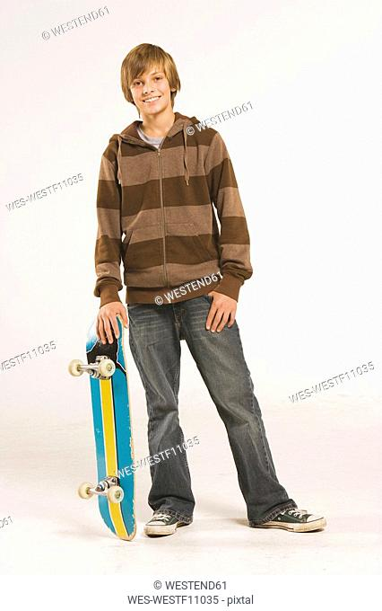 Teenage boy 13-14 standing with skateboard over head, smiling