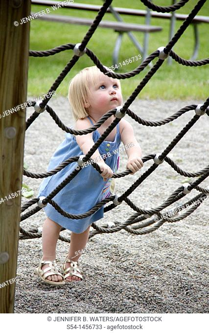 A toddler at the park, climbing a rope net