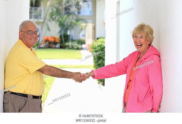 Senior couple smiling at doorway and holding each other's hands