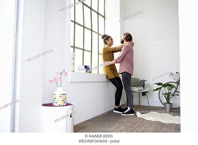 Young couple embracing in new flat
