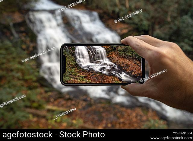 Person holding a cell phone taking a picture of Merry Falls - DuPont State Recreational Forest - Cedar Mountain, near Brevard, North Carolina