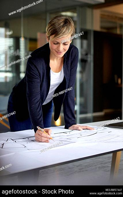 Woman working on construction plan in office