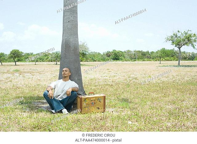 Man with suitcase sitting on the ground, leaning against tree with eyes closed