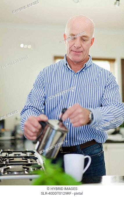 Older man pouring cup of coffee
