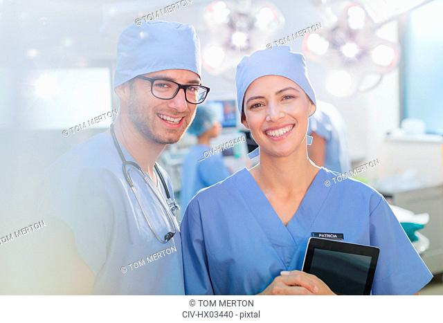 Portrait smiling, confident surgeons with digital tablet in operating room
