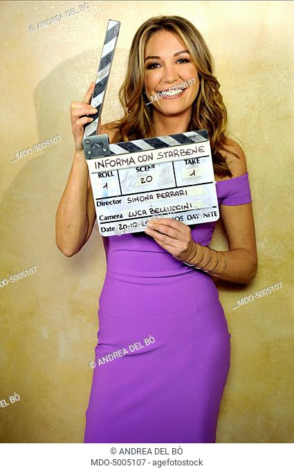 TV host Tessa Gelisio posing with a clapperboard on a photoshooting after the second episode of TV show In forma con Starbene