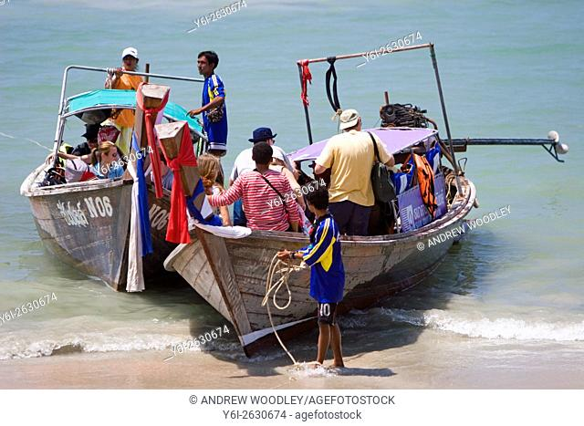 Visitors board long tail boats on Ao Nang Beach to get to other beaches and resorts Thailand