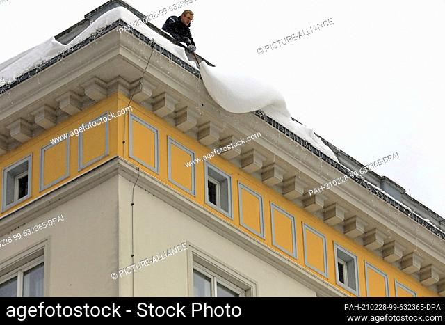 09 February 2021, Saxony-Anhalt, Magdeburg: A man releases overhanging snow slabs from a roof. His colleague secures the footpath