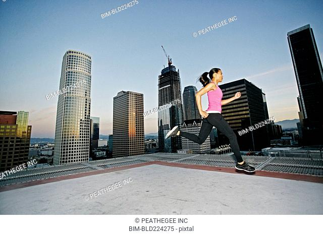 Mixed Race woman running on urban rooftop
