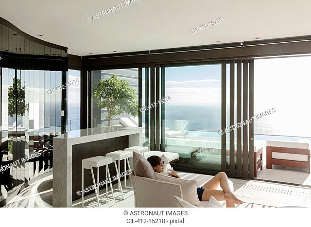 Woman relaxing in modern living room overlooking ocean