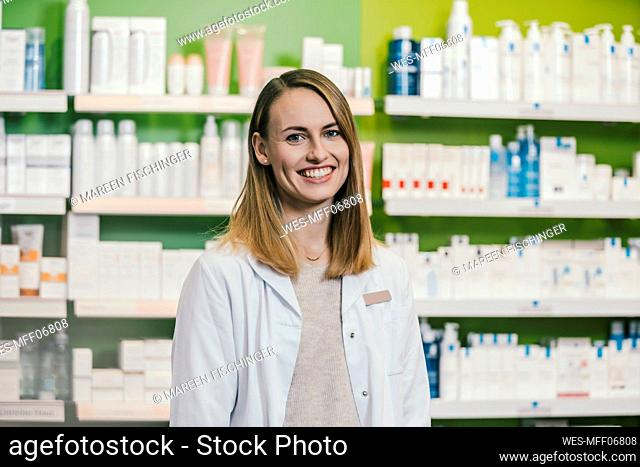 Confident pharmacist wearing lab coat while standing in chemist shop