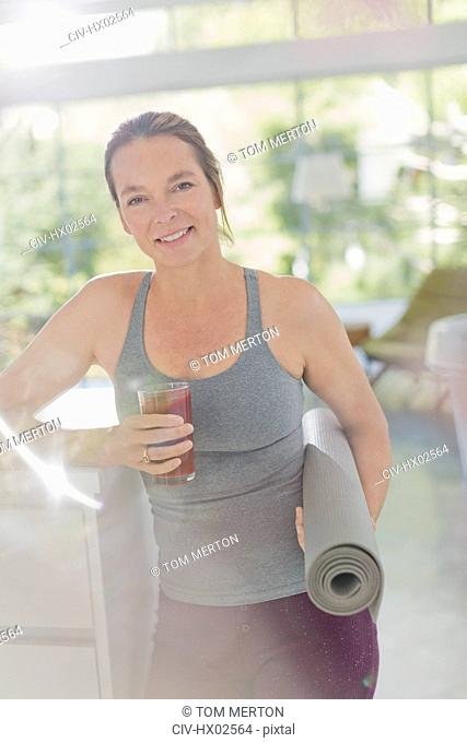 Portrait smiling mature woman with yoga mat drinking juice smoothie