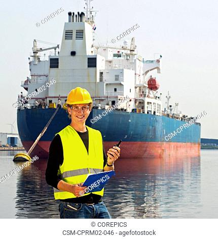 Smiling docker with clipboard and cb radio, posing in front of a large oil tanker