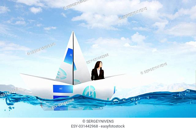 Successful businesswoman sailing on paper boat in financial sea