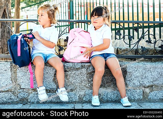 A black-haired girl wearing a pink backpack and a blonde-haired girl wearing a blue backpack next to the school. School concept