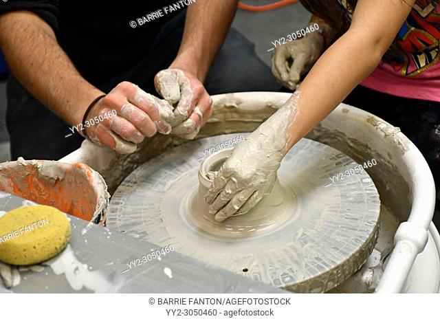 Adult Potter Assisting Young Student in Using Pottery Wheel, Wellsville, New York, USA