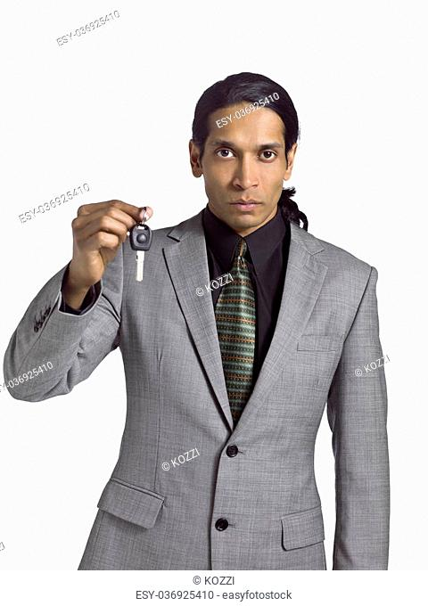 Matured asian businessman holding a key over a white background