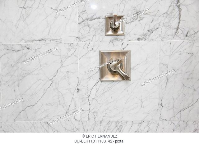 Close-up of shower taps on marble wall in the bathroom at home; Irvine; California; USA