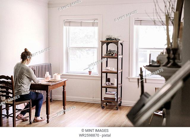 Woman sitting at a table in her apartment, writing in a diary, morning routine