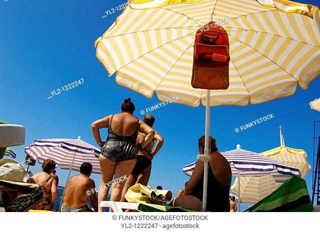 Sunbathers sitting on sun beads looking at the sea  Piran , Slovenia