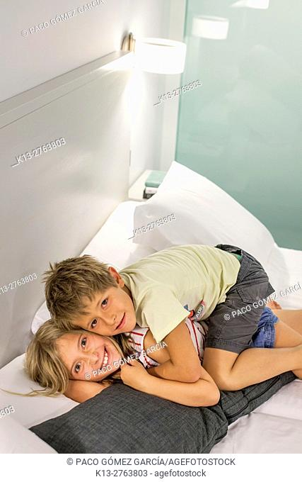 Brother and sister having a pillow fight on the bed