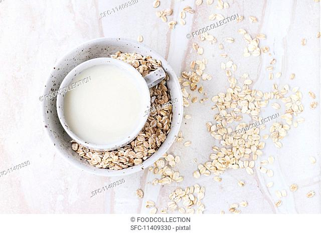 A cup of oat milk in a bowl of oats on a marble surface (seen from above)