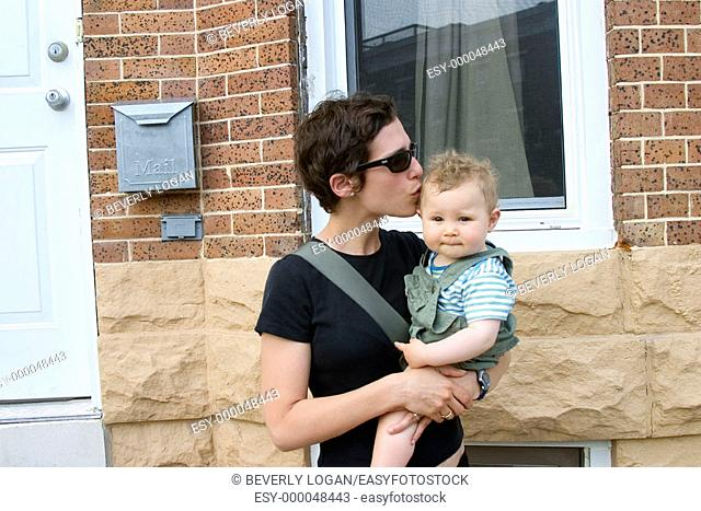 Mother and baby in front of a rowhouse in Baltimore. Maryland, USA