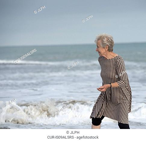 Senior woman running from ocean wave on beach, Dana Point, California, USA