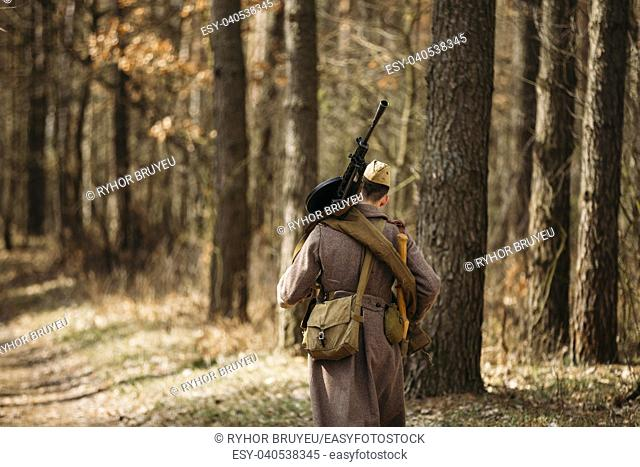 Young unidentified re-enactor dressed as Soviet soldier machine gunner goes along a forest road