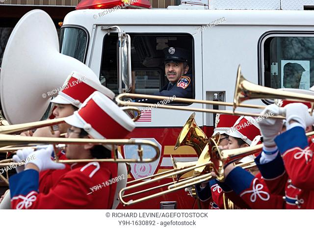 FDNY firefighter watches IS 318 marching band in the annual Three Kings Day Parade in the Bushwick neighborhood of Brooklyn on Sunday, January 8
