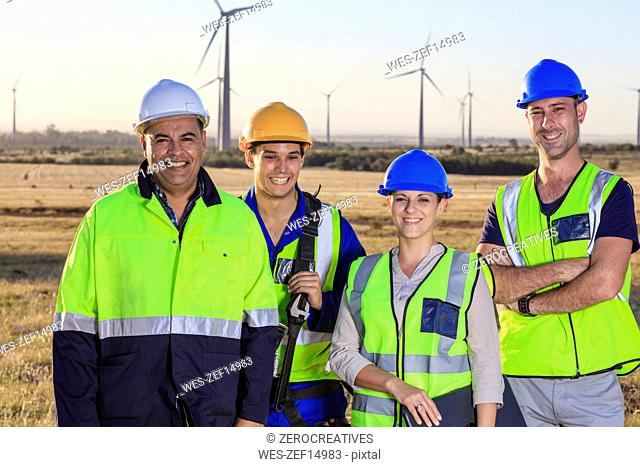 Portrait of four smiling engineers on a wind farm