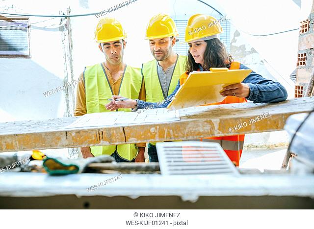 Woman talking to two construction workers on construction site