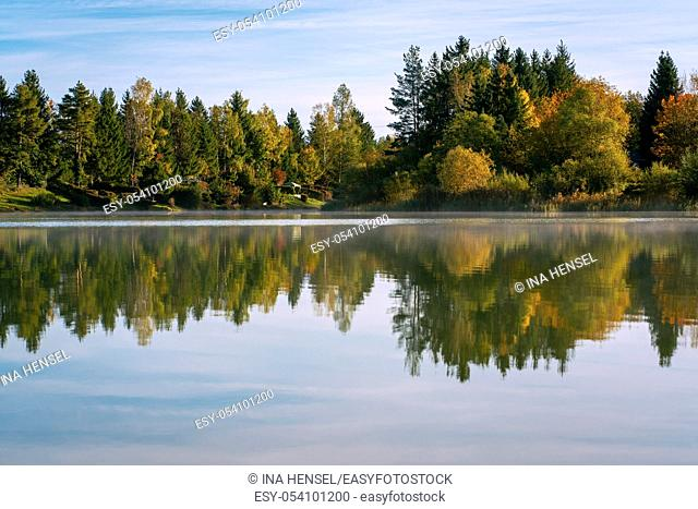 Lake Bibi (Bibisee) in Bavaria in autumn with reflexions of multi coloured t and a blue sky aboverees on the water surface