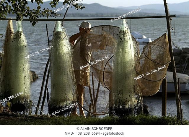 Mid adult man adjusting fishing net on a wooden stick, San Feliciano, Lake Trasimeno, Umbria, Italy