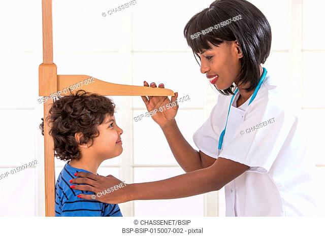 Doctor measuring the height of a boy