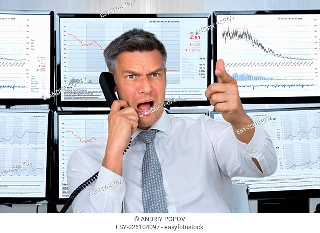 Angry male stock trader shouting while using telephone with computer screens in background
