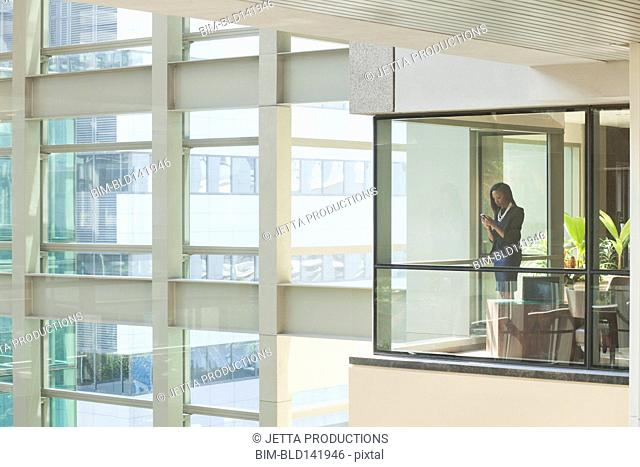 African American businesswoman standing at office window