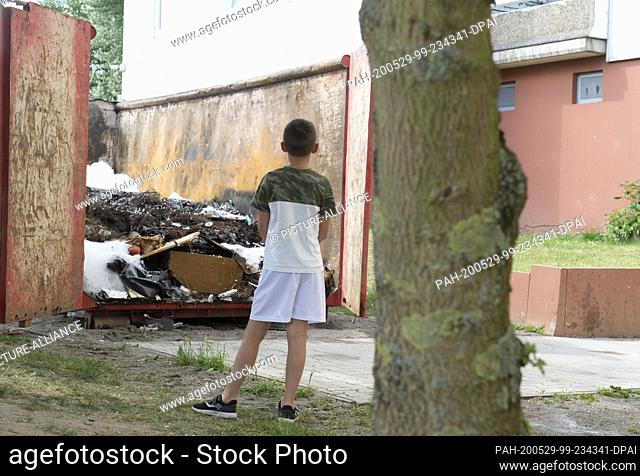 29 May 2020, Dietzenbach: After violent attacks on police and firefighters, a boy stands in front of a high-rise building in front of which the attacks had...