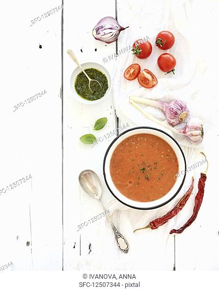 Gazpacho soup in rustic metal bowl with fresh tomatoes, green sauce, chili, garlic and basil over rustic white wooden backdrop