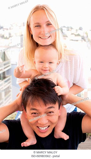 Portrait of parents with baby son on shoulders in front of window