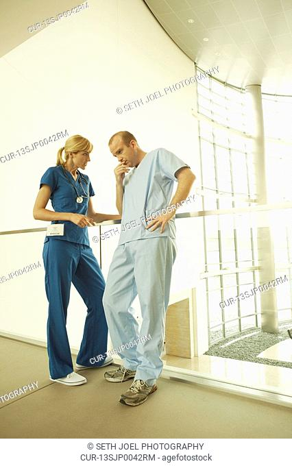 Doctor and nurse in scrubs discussing care in corridor overlooking lobby of modern hospital or clinic
