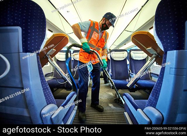 05 June 2020, North Rhine-Westphalia, Dortmund: An employee of the DB-Fernverkehrswerk Dortmund wearing face masks and rubber gloves uses a vacuum cleaner to...