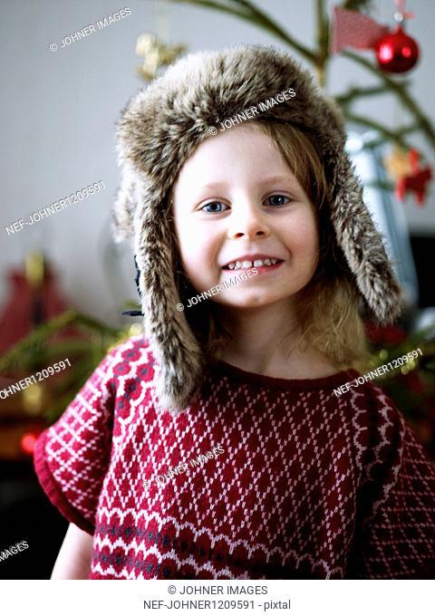 Portrait of girl wearing fur hat, christmas tree in background