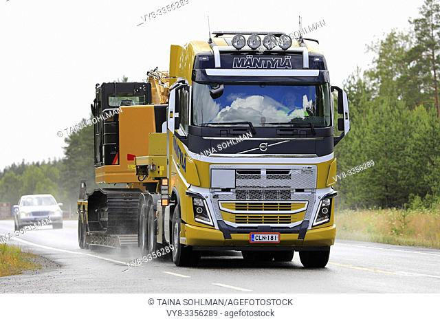 Raasepori, Finland. July 5, 2019. Volvo FH16 semi trailer of E & E Mantyla Ky hauls Cat 325F hydraulic excavator as wide load on wet highway in rain