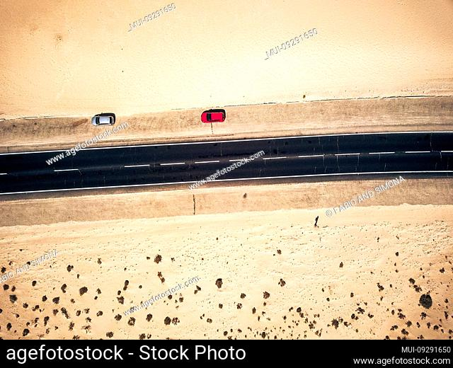 Aerial view of black straight asphalt road with sand and desert on both sides around - two car parked on the side - concept of travel and wanderlust for exotic...
