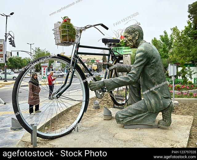 Street scene - women walk past a sculpture that represents an oversized man with his bike, taken on April 25, 2017 in the Iranian city of Isfahan