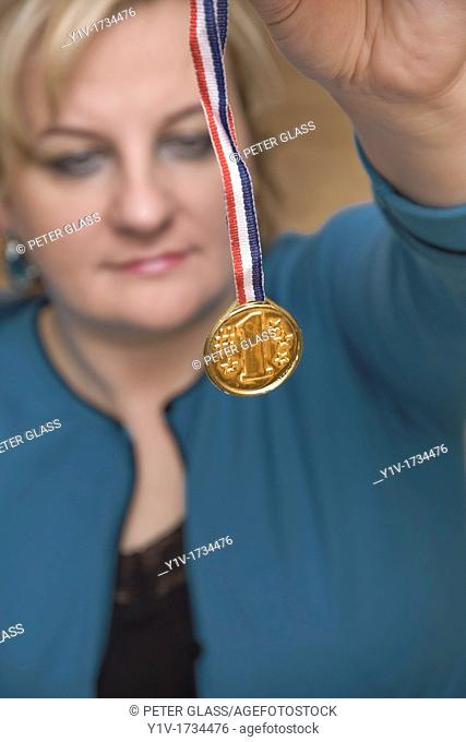 Blonde woman holding a 1st Place medal